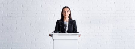 Photo for Attractive, confident lecturer holding on podium tribune in conference hall - Royalty Free Image