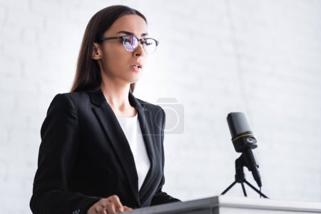 Photo for Serious young lecturer in glasses and formal wear standing on podium tribune - Royalty Free Image
