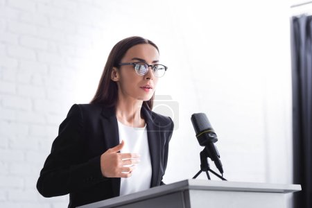 Photo for Pretty, young lecturer in formal wear in glasses speaking from podium tribune - Royalty Free Image