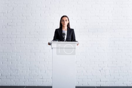 Photo for Beautiful, confident lecturer standing on podium tribune near white brick wall - Royalty Free Image