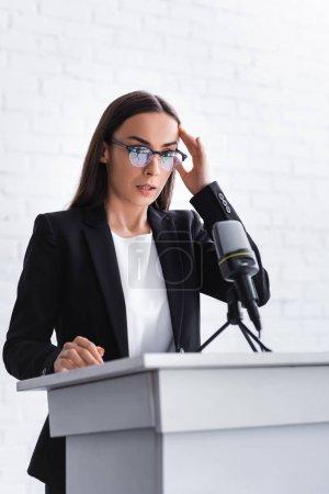 Photo pour Jeune conférencier souffrant de la peur de parler en public debout sur la tribune podium et tenant la main près de la tête - image libre de droit