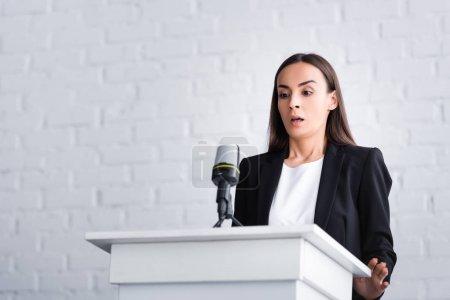 Photo pour Conférencier effrayé souffrant de la peur de parler en public tout en se tenant sur la tribune podium - image libre de droit