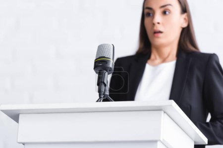 Photo for Selective focus of scared young lecturer, suffering from fear of public speaking, standing near microphone on podium tribune - Royalty Free Image