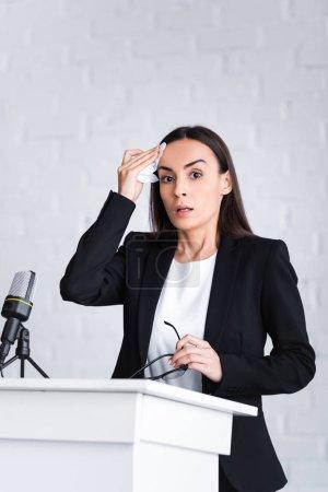 Photo pour Conférencier nerveux souffrant de la peur de parler en public tenant serviette et regardant la caméra tout en restant sur la tribune de podium - image libre de droit