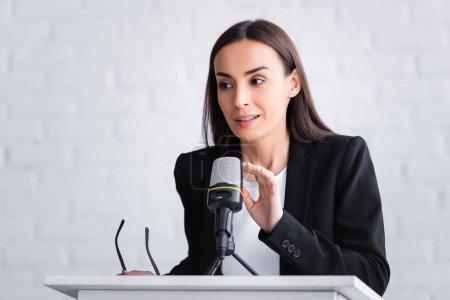 Photo pour Joli, souriant conférencier toucher microphone tout en restant sur la tribune podium - image libre de droit