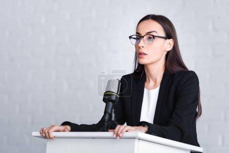 Photo pour Conférencier nerveux dans les lunettes debout sur la tribune podium et en regardant loin - image libre de droit