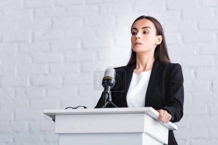 Photo pour Joli jeune conférencier souffrant de la peur de parler en public tout en se tenant sur le podium tribune - image libre de droit