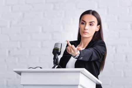 Photo for Dissatisfied lecturer standing on podium tribune in conference hall and showing middle finger - Royalty Free Image