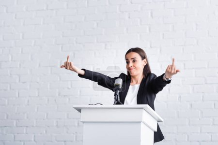 Photo for Irritated lecturer showing middle fingers while standing on podium tribune in conference hall - Royalty Free Image