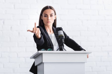 Photo for Irritated lecturer standing at podium tribune while showing middle finger at camera - Royalty Free Image