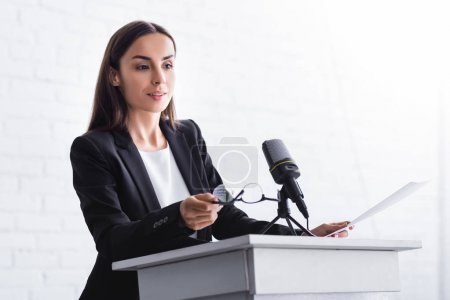 Photo for Beautiful, positive lecturer holding glasses while standing on podium tribune - Royalty Free Image