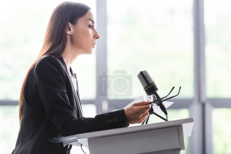 Photo for Serious lecturer holding glasses while standing on podium tribune in conference hall - Royalty Free Image