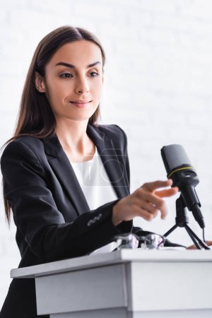 Photo for Smiling lecturer touching microphone while standing on podium tribune in conference hall - Royalty Free Image