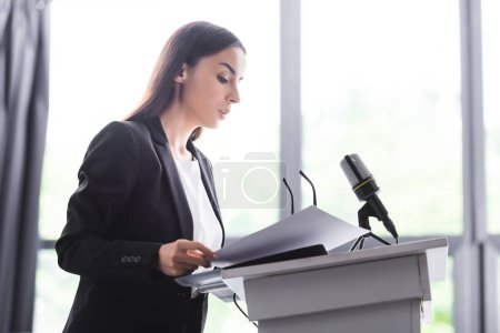 Photo for Attractive, attentive lecturer standing on podium tribune and looking at documents - Royalty Free Image
