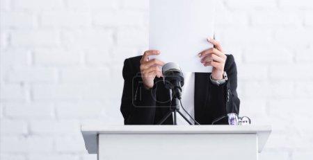 Photo pour Jeune conférencier, souffrant de la peur de parler en public, debout sur la tribune podium et se cachant la face derrière une feuille de papier - image libre de droit