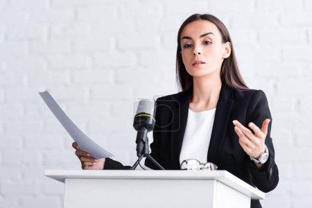 Photo pour Conférencier confiant geste tout en parlant dans le microphone sur le podium tribune - image libre de droit