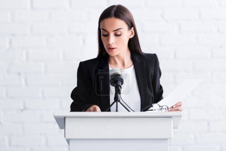 Photo for Attractive young lecturer standing on podium tribune and looking at papers - Royalty Free Image
