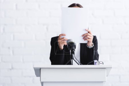 Photo for Scared lecturer suffering from logophobia and hiding face behind paper while standing at podium tribune - Royalty Free Image