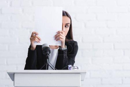 Photo pour Jeune conférencier souffrant de la peur de parler en public se cachant visage avec une feuille de papier tout en restant sur la tribune podium - image libre de droit