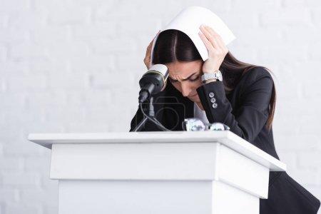 Photo pour Jeune conférencier, souffrant de la peur de parler en public, debout sur la tribune podium et couvrant la tête avec du papier - image libre de droit