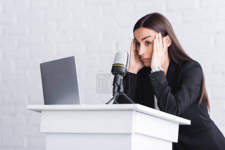 Photo pour Conférencier effrayé restant sur la tribune de podium et se tenant la main près de la tête - image libre de droit