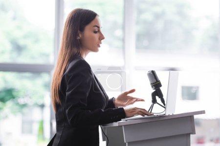Photo pour Attrayant, confiant conférencier geste tout en parlant de tribune podium - image libre de droit