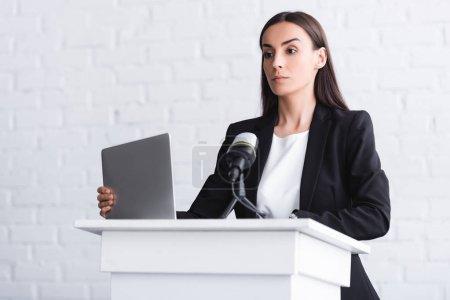 Photo pour Conférencier attrayant et confiant restant sur la tribune de podium près du microphone et de l'ordinateur portatif - image libre de droit