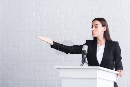 Photo for Attractive, confident lecturer pointing with hand while standing on podium tribune - Royalty Free Image