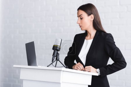 Photo for Serious lecturer standing on podium tribune near microphone and laptop - Royalty Free Image