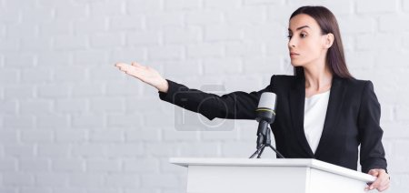Photo for Panoramic shot of beautiful, serious lecturer pointing with hand while standing on podium tribune - Royalty Free Image