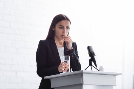 Photo pour Jeune conférencier souffrant de l'anxiété de la parole debout sur la tribune podium avec un verre d'eau - image libre de droit