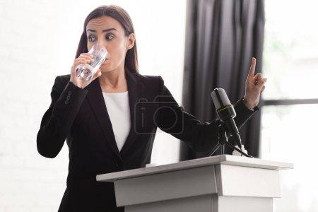 Photo pour Conférencier inquiet montrant geste d'attente tout en restant sur la tribune de podium et l'eau potable - image libre de droit