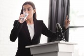 "Постер, картина, фотообои ""worried lecturer showing wait gesture while standing on podium tribune and drinking water"""