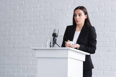 Photo pour Joli conférencier, souffrant de glossophobie, debout sur la tribune podium et contenant de retenue avec des pilules - image libre de droit