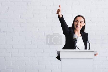 Photo pour Conférencier heureux et attrayant affichant le pouce vers le haut tout en restant sur la tribune de podium - image libre de droit