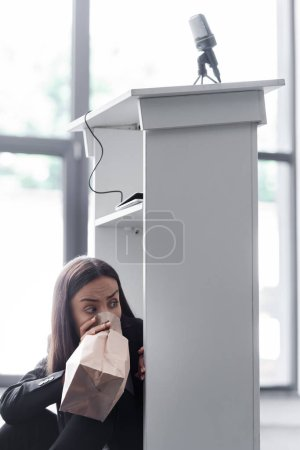Photo for Frightened lecturer breathing into paper bag while sitting on floor in conference hall and suffering from panic attack - Royalty Free Image