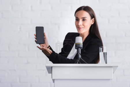 Photo for Cheerful lecturer standing on podium tribune and presenting smartphone with blank screen - Royalty Free Image