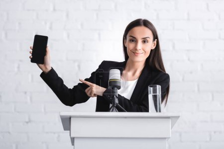 Photo for Smiling lecturer standing on podium tribune and pointing with finger at smartphone with blank screen - Royalty Free Image