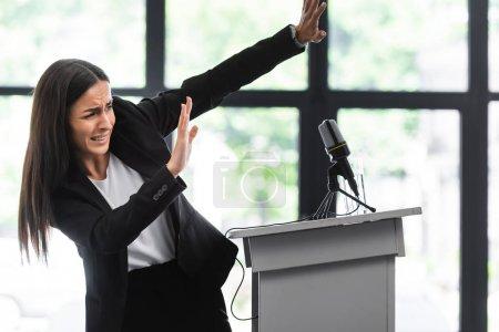 Photo pour Conférencier effrayé souffrant de la peur de parler en public gesticulant avec les mains tout en se tenant sur la tribune podium dans la salle de conférence - image libre de droit