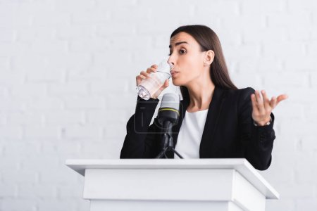 Photo for Pretty, young lecturer drinking water and gesturing while standing on podium tribune - Royalty Free Image