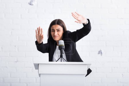 Photo for Frightened lecturer suffering from glossophobia gesturing with hands while standing on podium tribune - Royalty Free Image