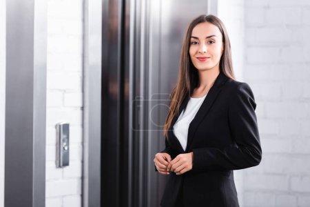 Photo pour Belle femme d'affaires souriant à l'appareil-photo en attendant l'ascenseur - image libre de droit