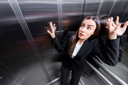 Photo for Young scared businesswoman suffering from claustrophobia in elevator - Royalty Free Image