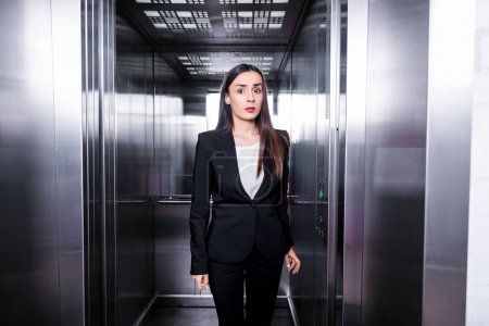 Photo for Young businesswoman, suffering from claustrophobia, standing in elevator and looking at camera - Royalty Free Image