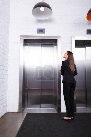 Photo pour Vue arrière de la femme d'affaires dans l'usure formelle restant dans le hall et attendant l'ascenseur - image libre de droit