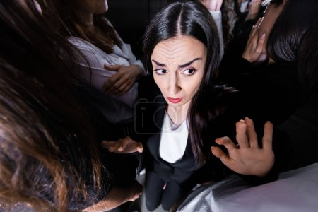 Photo for Overhead view of businesswoman suffering from claustrophobia in crowded elevator - Royalty Free Image