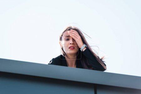 Foto de Mujer de negocios asustada, que sufre de acrofobia, mirando hacia abajo en la azotea y cubriendo la cara con la mano - Imagen libre de derechos