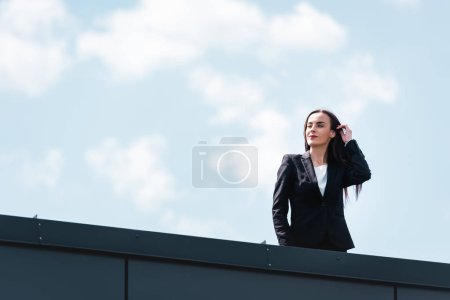 Photo for Attractive businesswoman standing on rooftop, smiling an looking away - Royalty Free Image