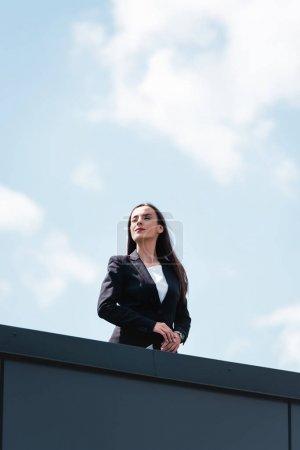 Photo pour Attrayant, confiant femme d'affaires souriant et détournant les yeux tout en se tenant sur le toit - image libre de droit