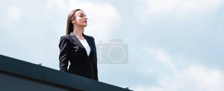 Photo for Beautiful, confident businesswoman standing on rooftop, smiling and looking away - Royalty Free Image